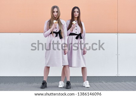 portrait of two  sister girls, eating ice cream cone, sure poker faces, grimaces,  no emotions, casual style, bright colors, orange white wall.  hipster girl #1386146096