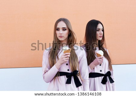 portrait of two  sister girls, eating ice cream cone, sure poker faces, grimaces,  no emotions, casual style, bright colors, orange white wall.  hipster girl #1386146108