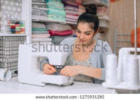 portrait of young woman seamstress sitting and sews on sewing machine. Tailor making a garment in her workplace. Hobby as a small business concept