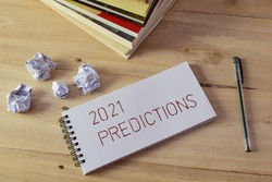 2021 PREDICTIONS handwritten on notebook laid on wooden desk with books, pen and crumbled paper balls. Concept of analyzing future events, selective focus.