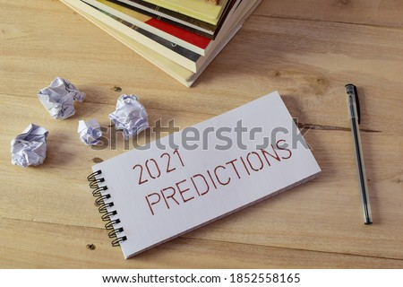2021 PREDICTIONS handwritten on notebook laid on wooden desk with books, pen and crumbled paper balls. Concept of analyzing future events, selective focus. ストックフォト ©