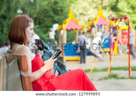 pregnancy woman reads e-book against  playground area - stock photo