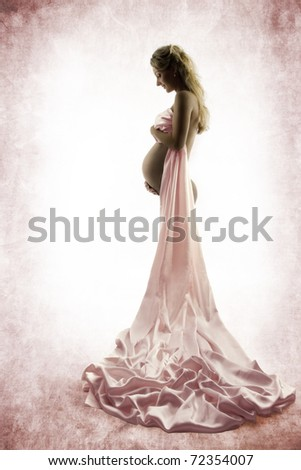 Pregnant woman looking at belly. Silk dress, cloth.  Grunge background. Vintage style.