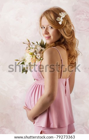 Pregnant woman smiling, looking at camera, holding flowers. Pink dress.