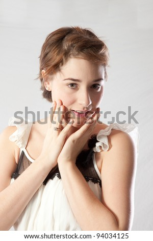 Pretty Caucasian woman with eye contact, her hands on her cheeks and a friendly smile