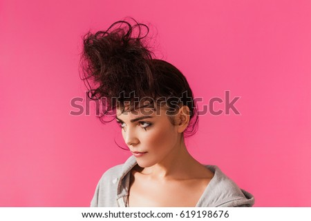 Pretty woman with messy bun wearing hoodie and looking aside #619198676