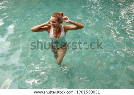 Pretty young woman in white swisuit  relaxing in outdoor spa swimming pool. Beauty and body care. stock photo