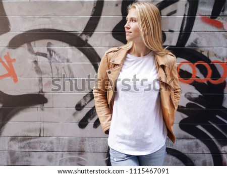Pretty young woman with a long blond hair standing on a street with the bright wall background. Mock up.
