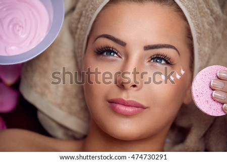 Pretty young woman with facial mask at beauty salon