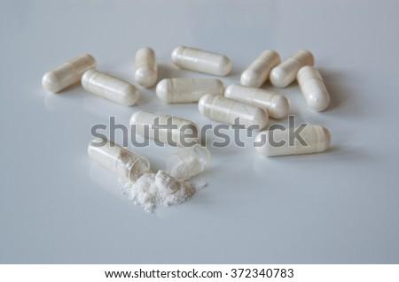 Probiotics. White medicine capsules probiotic powder inside, one capsule open.