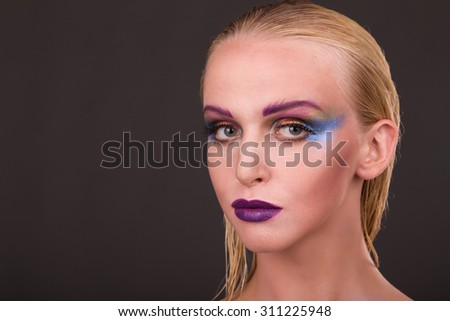 Professional makeup. Art makeup. Bright and unusual make-up on beautiful model. Beautiful blonde on a dark background. Portrait photo.