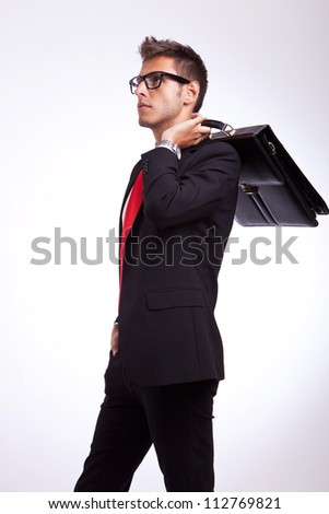 profile of a young business man or student looking to his side with suitcase on his shoulder