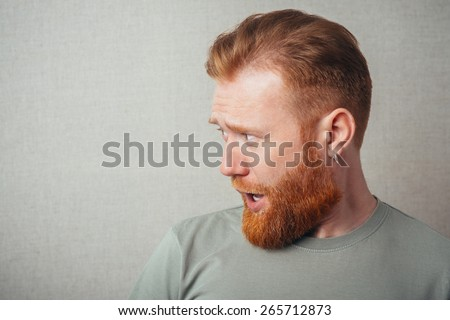 Profile of Young hipster red bearded Man standing against grey background