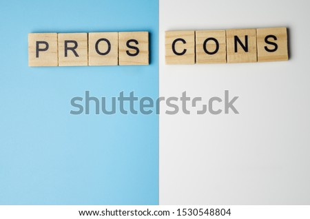 """""""Pros and Cons"""" word in the wooden block on duo color background"""
