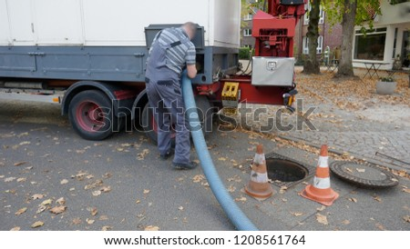 Pumping off the sewage tank of a mobile sanitary container into the sewage system  #1208561764