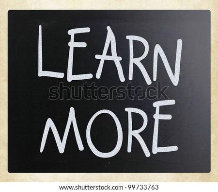 """Learn More"" handwritten with white chalk on a blackboard - stock photo"