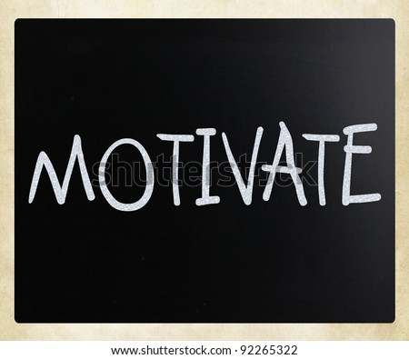 """Motivate&quot ; handwritten with white chalk on a blackboard - stock photo"