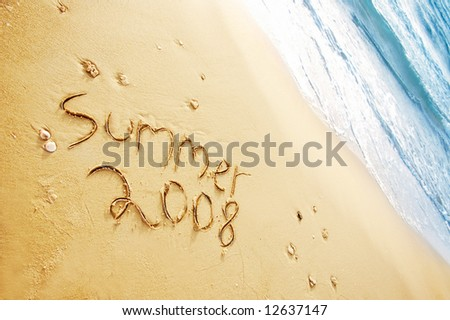 """""""summer 2008"""" written in the sand on the beach blue waves in the background - stock photo"""