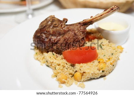 Rack of lamb with couscous on porcelain plate, copy space
