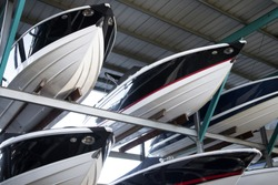 Rack of modern speedboats for sale, with pointed fiberglass hulls and bows, in a covered warehouse at a maritime storage dockyard