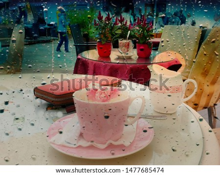 Rain Street Cafe on table cup of coffee and pink flowers  pink coral tablecloth on the table and yellow chair cloth rainy season  #1477685474
