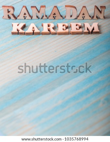 'Ramadan Kareem' words the Islamic fasting month of Ramadhan greetings meaning 'Generous Ramadan' on blue wooden table top #1035768994