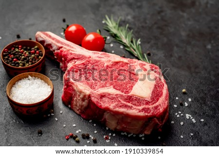 Raw cowboy steak with spices on stone background Foto stock ©