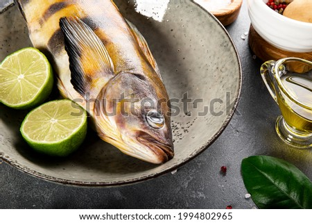 Raw fish sea bass or lingcod and seasonings for cooking it on a table close up Photo stock ©
