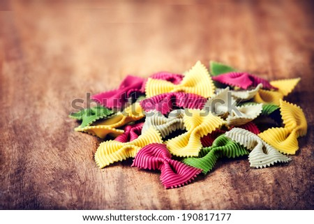 Raw Italian Pasta on wooden table with copyspace for text.  Raw Bow tie Colourful  pasta macro. Italian Food.