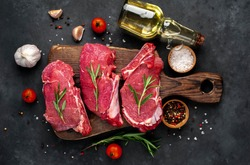 raw three beef steaks on a cutting board with spices on a stone background