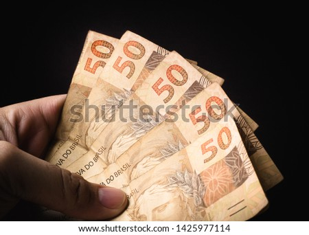 Real - BRL, Money from Brazil. Reais, Dinheiro, Brasil. A Man holding a brazilian banknotes in hand. Foto stock ©