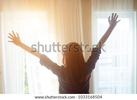 Rear view of a woman in plaid shirt standing near the window while stretching near bed after waking up with sunrise at morning,Beautiful woman looking outside the window in her beautiful apartment, #1033168504