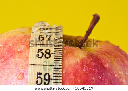 Red apple and measuring tape, isolated on yellow