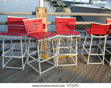 4 red chairs at pier