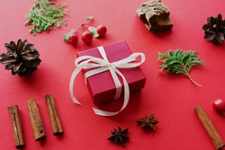 red gift box with ribbon with natural Christmas decor - cinnamon sticks, fir tree branches, anise stars and bark fragments. Concept of Christmas and New Years holidays. Copy space