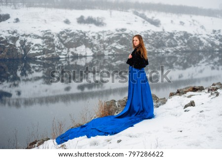 red-haired curly-haired girl on a winter walk in the snow on nature in the park