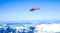 Red helicopter in the sky over the Alpine mountains, a beautiful mountain landscape, air transport movement