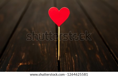 Red paper heart on a stick Against the background of an old tree, Valentine's Day #1264625581