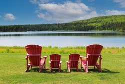 red plastic adirondak chairs in front of the beautiful  view at Wolfe Lake in Fundy National Park in New Brunswick, Canada