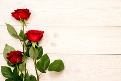 3 red roses on white aged table
