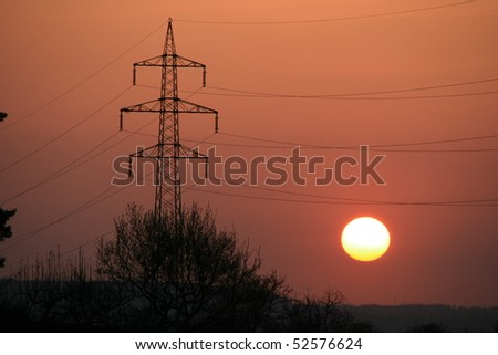 red sun and powerline - stock photo