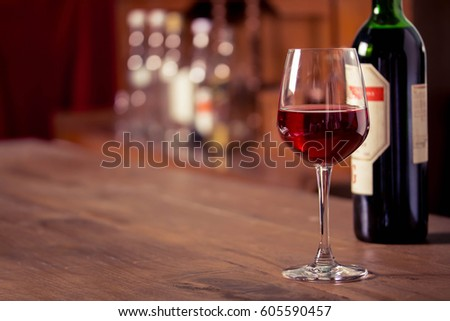 red wine into the glass against wooden background #605590457