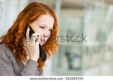 Redhead girl speaking by phone. Selective focus with shallow depth of field.