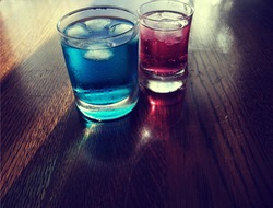 2 refreshing cold blue and red soda drinks with lots of ice. Soda drinks are in small glasses. Soda drinks are transparent and some bubbles can be seen. 2 reflections can be seen on the wood.