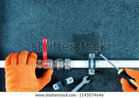 Repair plumbing pipes background.Hand plumber holding faucet, tools for repair plumbing.