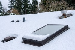 Residential house rooftop covered in fresh snow, skylight, roof vents, evergreen trees