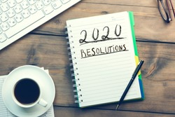 2020 resolutions text on notepad with computer on office desk
