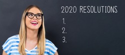 2020 Resolutions with happy young woman in front of a blackboard