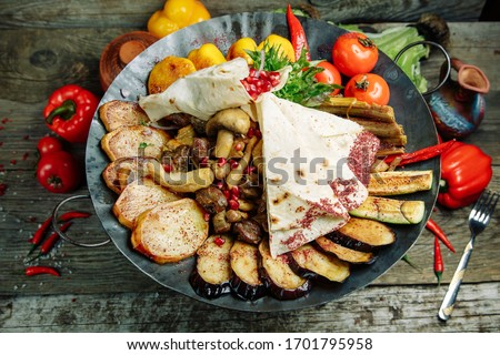 Restaurant dish on a wooden background. Azerbaijani saj with meat and vegetables.
