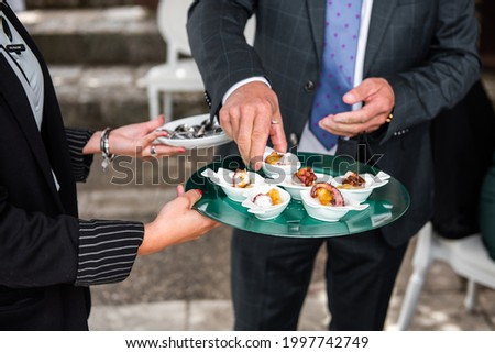 104  5000Resultados de traducciónclose-up of hands picking up food from a tray being served by the waiter at an event Stockfoto ©